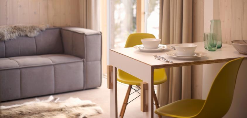 Bright yellow vitra chairs with folding kitchen table and modern sofa, Architect designed holiday cottage near Edinburgh, Scotland